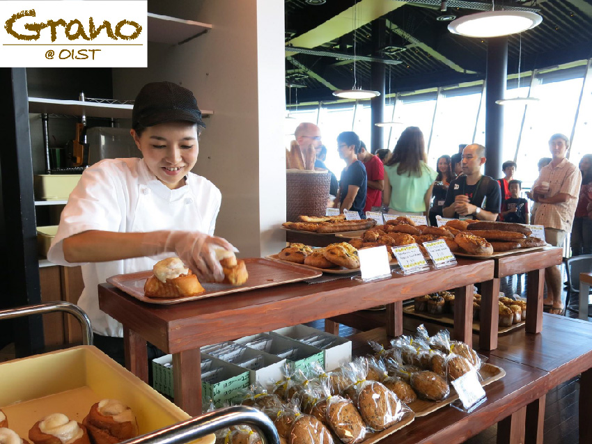 Photo of woman putting bread on the rack in cafe